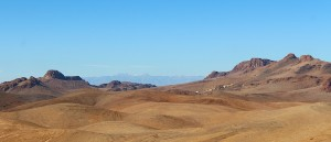 Heat and sand in the foreground, snow-capped mountains in the distance