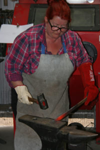 Girl with large hammer and searing hot metal