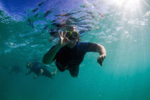 Happily snorkelling with Geoff in the background